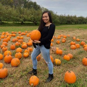 Photograph of Kelly Garcia in a field of pumpkins